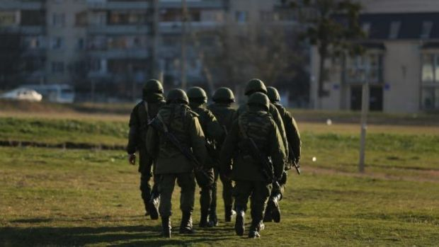 Russian soldiers march towards residential buildings near the Ukrainian marine military base at Perevalnoye in Crimea. ...