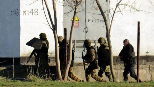 Armed Russian forces take part in a military operation at a Ukrainian military base in Simferopol.