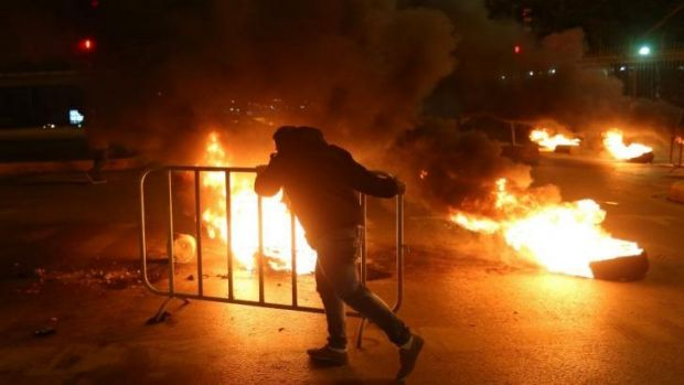 "A Sunni man blocks a major road between Beirut and the capital's southern suburbs in protest over the ""siege"" of the ..."