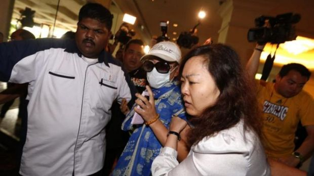 A woman, centre, is forcibly removed by security officials after she tried to protest before a press conference ...