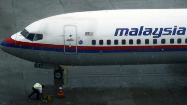Ground staff work on a Malaysia Airlines aircraft at the Kuala Lumpur International Airport.