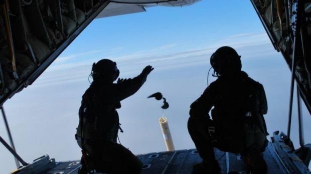 Loadmasters Sergeant Adam Roberts (left) and Flight Sergeant John Mancey launch one of two water-activated buoys from ...