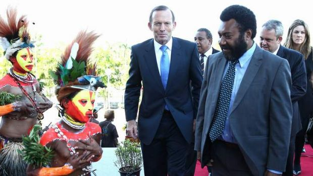 Prime Minister Tony Abbott is greeted by Singsing dancers on his arrival at Parliament House in Port Moresby.