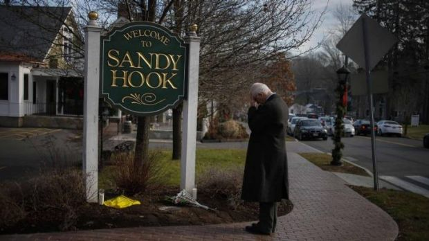 A man pauses to mourn at the entrance to the town of Sandy Hook on December 15, 2012, in the immediate aftermath of the ...
