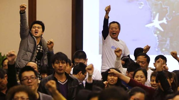 """""""Return our families"""": Family members of passengers onboard MH370 raise their fists in protest at a government briefing ..."""