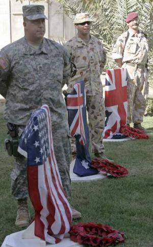 American, Australian, and British soldiers stand beside their national flags during a Remembrance Day ceremony at the ...