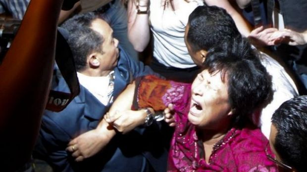 Liu Guiqiu is carried from a press conference by security officials in Malaysia.