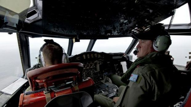 Royal Australian Air Force Flight Engineer, Warrant Officer Ron Day keeps watch for any debris as he flies in an AP-3C ...