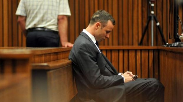 Staying connected ... South African Paralympic athlete Oscar Pistorius texts on his mobile phone as he sits in the dock ...