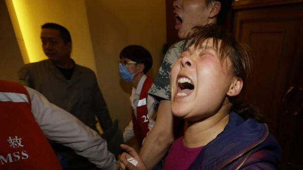 A distraught family member of a passenger aboard Malaysia Airlines MH370 shouts at journalists after watching the ...