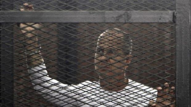 Australian journalist Peter Greste stands in a metal cage during his trial in a Cairo court.