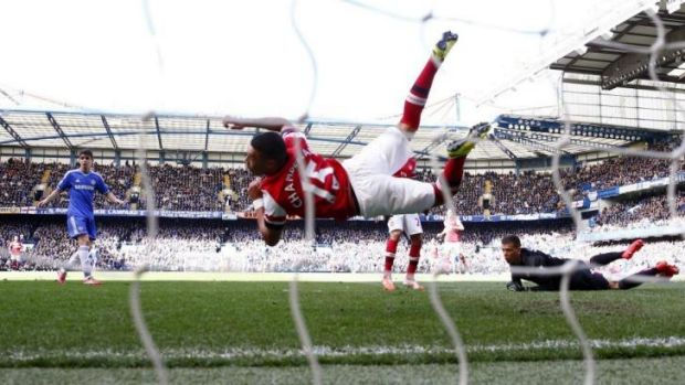 Arsenal outfielder Alex Oxlade-Chamberlain dives to save a shot at goal by Chelsea with his hand.