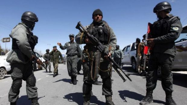 Armed response: Afghan police stand guard near the scene of the attack.