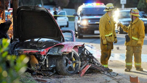 Firefighters next to the wreckage of the Porsche that crashed  killing Paul Walker and Roger Roda in November 2013.