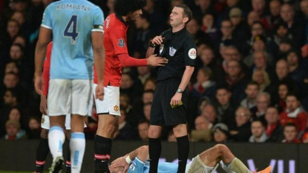 Michael Oliver talks to Marouane Fellaini after an incident with Pablo Zabaleta (prone).