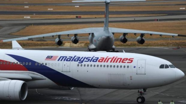 Mystery: A Malaysia Airlines plane prepares to go onto the runway and pass by a stationary Chinese Ilyushin 76 search ...
