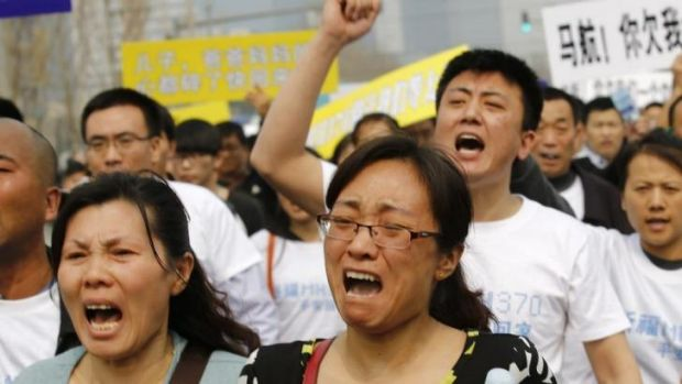 Distraught: Family members of passengers on board Malaysia Airlines MH370 shout slogans during a protest in front of the ...