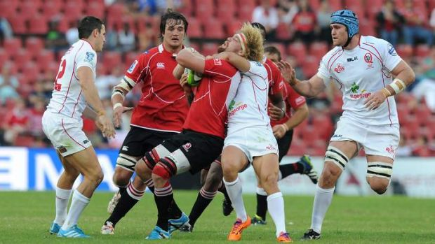 Willie Britz of the Lions is tackled by Quade Cooper at Ellis Park.