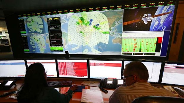 Staff at satellite communications company Inmarsat work in front of a screen showing subscribers using their service ...