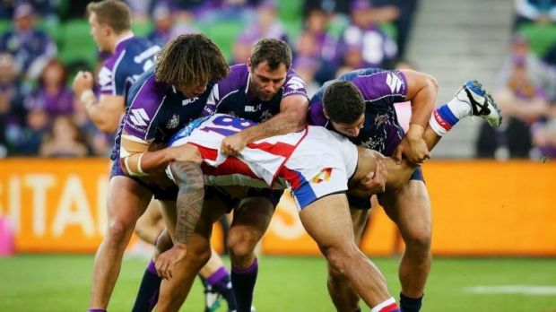 Three men in: David Fa'alogo is tackled by Kevin Proctor, Cameron Smith and Kenny Bromwich during the same match in ...