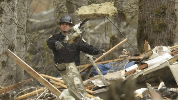 Massive task ... A worker throws debris while looking for victims in the mudslide near Oso.