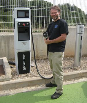 Chris Jones at an electric vehicle charging station.