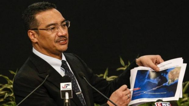 Malaysia's acting Transport Minister Hishammuddin Hussein holds satellite images as he speaks about the search for the ...