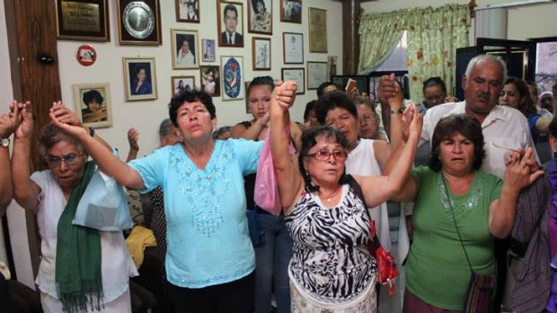 Relatives of Edgar Tamayo Arias pray in his parents' house.