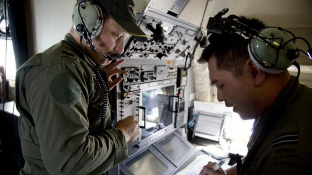 Crew members aboard a Royal Australian Air Force AP-3C Orion aircraft observe navigation maps as they search for missing ...