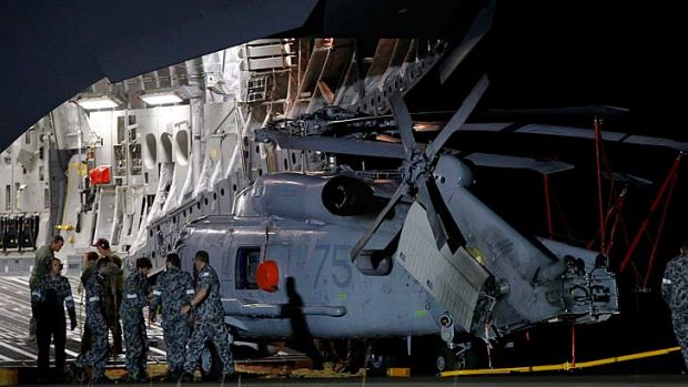 A Navy Seahawk helicopter is offloaded from a RAAF C17 Globemaster aircraft.