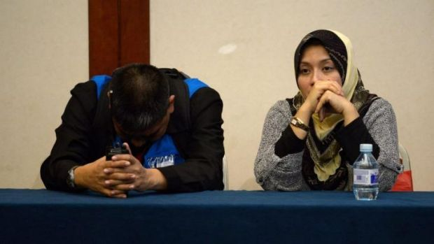 Strain on both sides ... Two members of the Malaysia Airlines special assistance team react as relatives of passengers ...