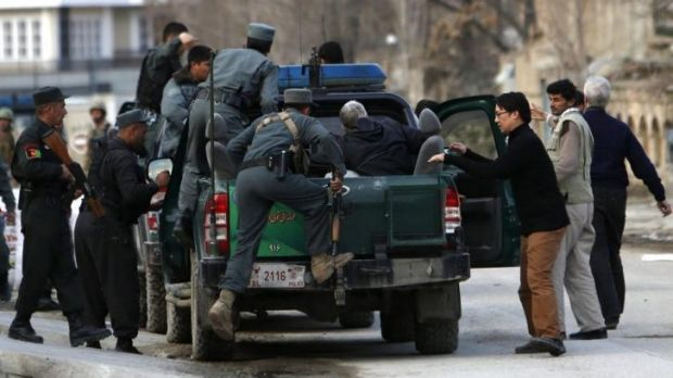 US charity targeted ... Afghan policemen evacuate foreigners from the site of the Taliban attack in Kabul.
