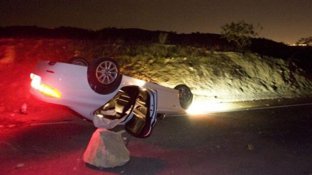 A car sits rolled over in the wake of Friday night's earthquake on Carbon Canyon Road in California.