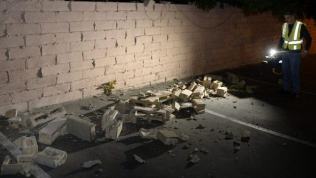 News cameraman Juan Guerra records a video of a fallen brick wall after a magnitude 5.1 earthquake in Fullerton, California.