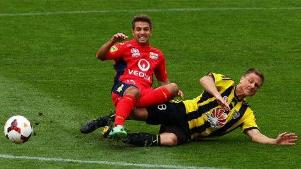 Physical contest: Ben Sigmund of the Phoenix tackles Michael Zullo of Adelaide United.