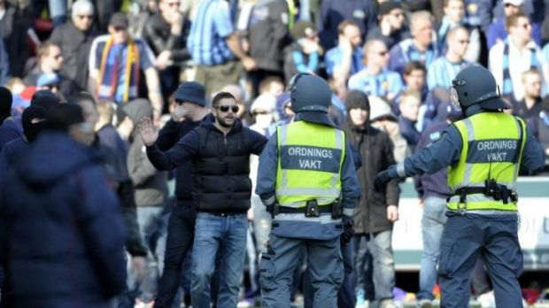 Security personnel try to control supporters of Stockholm club Djurgarden who stormed the pitch after hearing news of ...