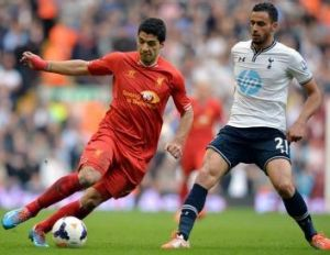 Liverpool's  Luis Suarez, left, takes on Tottenham Hotspur's  Nacer Chadli during Liverpool's 4-0 win.