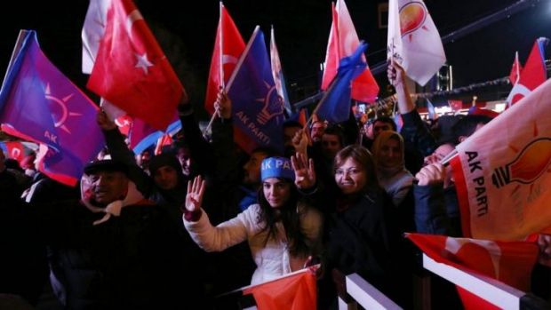 Loyalists: Supporters of the ruling AK Party celebrate in the streets of Ankara, with some holding up four fingers to ...