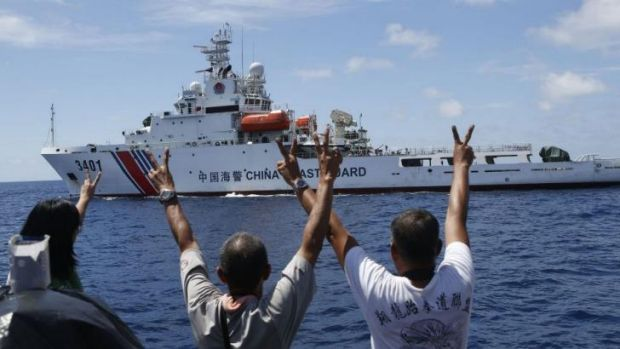 Philippines Marines and a television reporter on board a supply ship gesture towards a Chinese coastguard vessel near ...