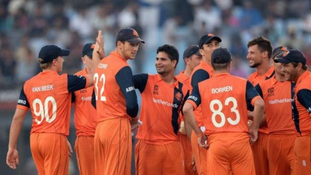 Netherlands bowler Mudassar Bukhari (centre) celebrates with his teammates after taking the wicket of England batsman ...