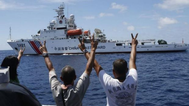 Philippine Marines and a local television reporter (left) gesture towards a Chinese Coast Guard vessel, which twice ...