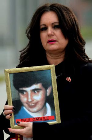 For some, the fight goes on: Outside the court, Donna Miller holds a picture of her brother Paul Carlile.