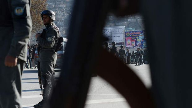 Police keep watch at the Afghan Ministry of Interior after a suicide bomb attack.