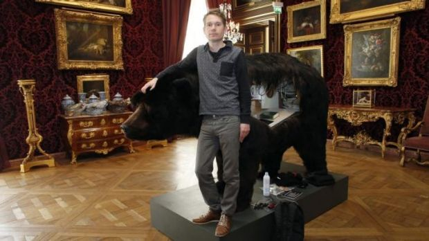 French artist Abraham Poincheval poses for a photograph next to the bear carcass on March 31, the day before starting a ...