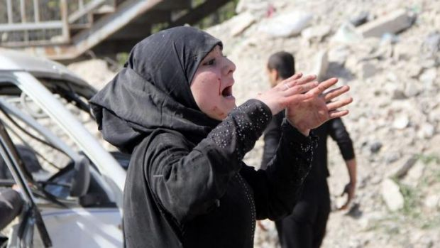 A Syrian woman reacts following an air strike by Syrian government forces in the al-Sakhour district of the northern ...