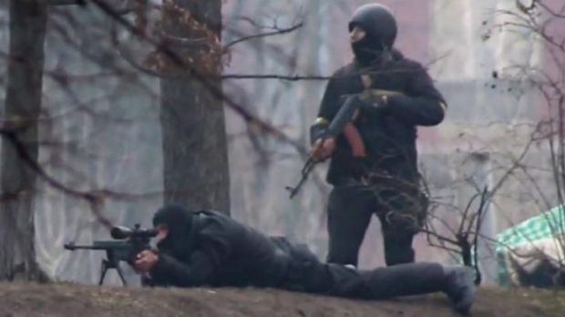 In cold blood: A riot policeman is seen standing next to a sniper in Kiev on February 20.