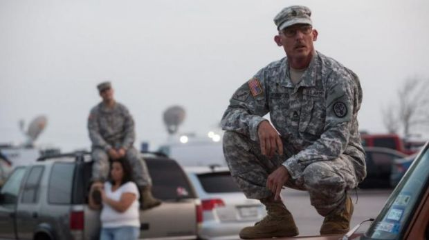 In shock ... Staff Sergeant John Robertson, right, waits in a parking lot outside of the Fort Hood military base for ...
