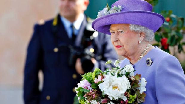 Britain's Queen Elizabeth II holds flowers as she leaves the Ciampino Airport in Rome April 3, 2014.