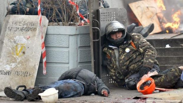 A wounded pro-European Maidan self-defence activist next to the bodies of people killed by snipers in Institutskaya ...