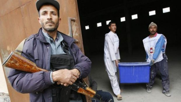 Contentious: Afghan election commission workers carry a ballot box as a police officer stands guard.